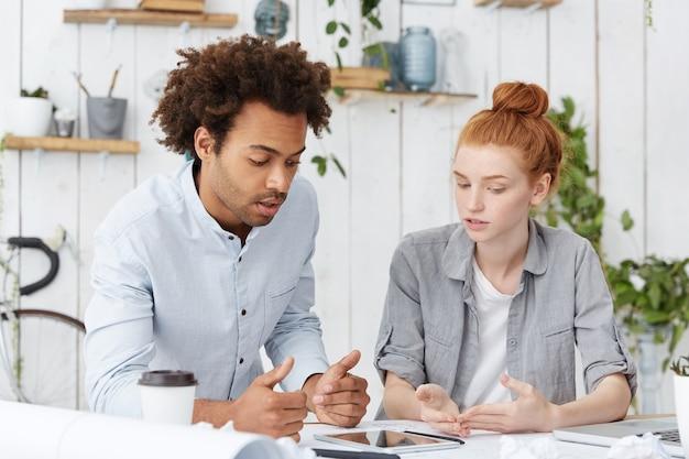 Equipe multiétnica de jovens arquitetos ambiciosos com pensamento criativo fazendo brainstorming na mesa branca