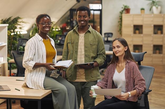 Equipe multiétnica de jovens empresários e sorrindo alegremente enquanto trabalham em um escritório moderno
