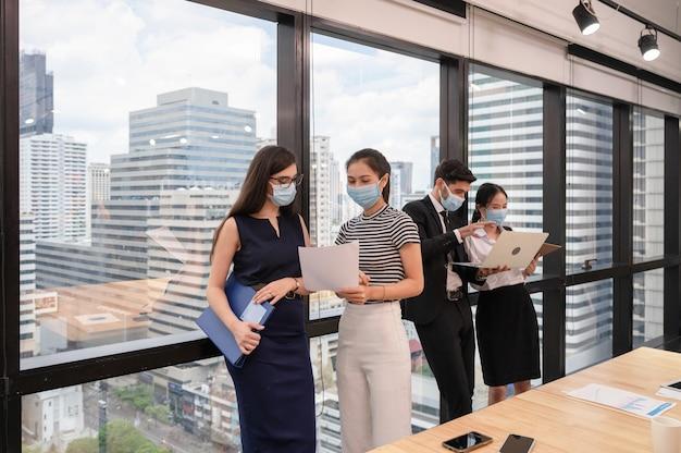 Equipe multiétnica de negócios, reunindo-se com a discussão e manutenção da papelada, laptop em um escritório moderno no centro da cidade. usando máscara facial de proteção contra pandemia de coronavírus, covid-19
