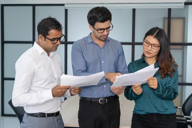 Equipe multiétnica do negócio que analisa relatórios financeiros.