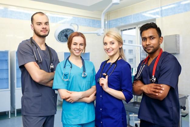 Equipe multirracial de jovens médicos em um hospital em pé na sala de cirurgia