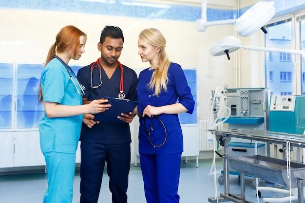 Equipe multirracial de médicos discutindo um paciente em pé em uma sala de cirurgia