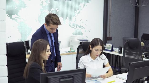 Equipe no trabalho. empresário em traje formal e duas mulheres - gerente e designer trabalhando em um novo projeto sentado diante de computadores no escritório