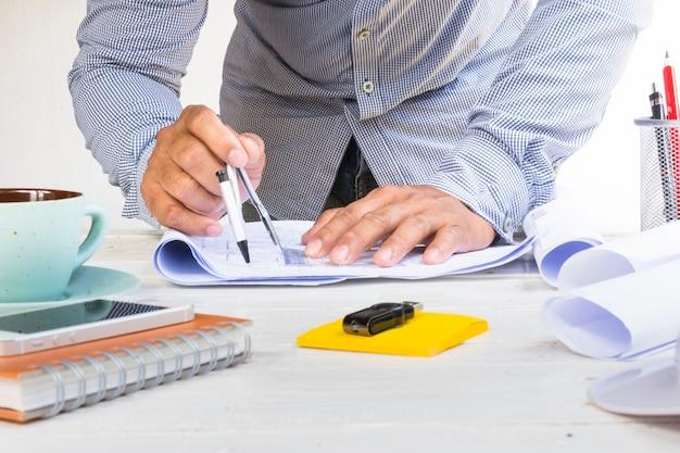 Equipe o arquiteto que usa o circo para o plano do projeto com equipamento na tabela branca.