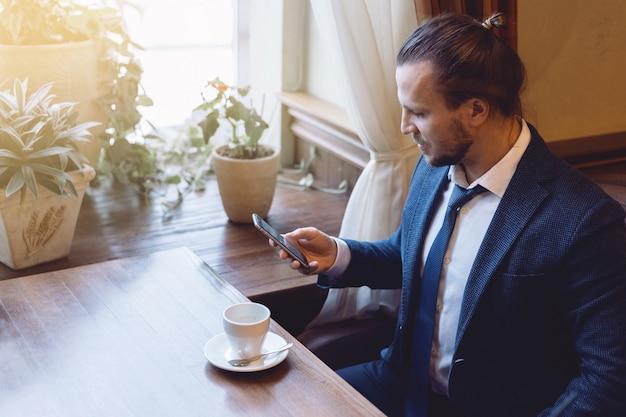 Equipe o assento na barra do café e a escrita de uma mensagem no telefone celular durante a ruptura de café.