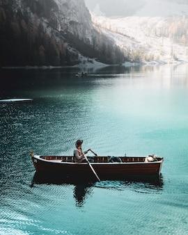 Equipe o barco de enfileiramento no lago azul de braies nas dolomites, tirol sul, itália.