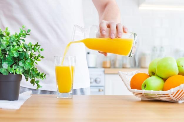 Equipe o suco de laranja de derramamento do jarro no vidro na cozinha.
