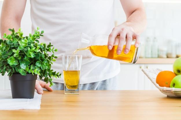 Equipe o suco de maçã de derramamento do jarro no vidro na cozinha.