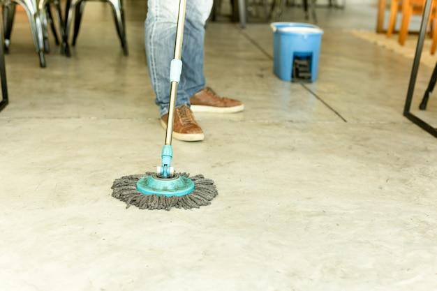 Equipe o trabalhador com o assoalho da limpeza do espanador e da cubeta no café.