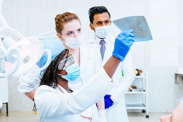 Equipe odontológica multirracial que verifica os dentes x raio-x do paciente. conceito de clínica dentária.