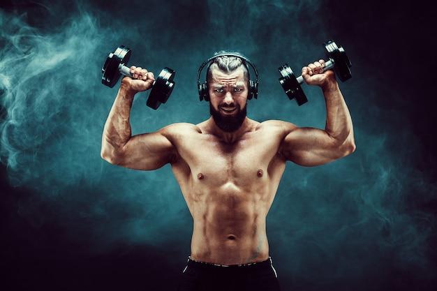 Equipe os músculos do treinamento com halteres no estúdio em fundo escuro com fumaça.