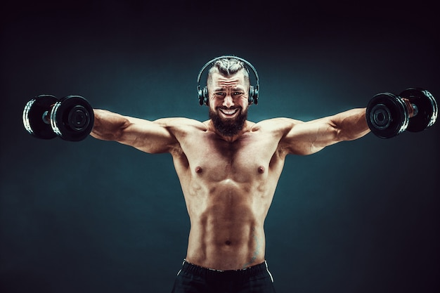 Equipe os músculos do treinamento com halteres no estúdio em fundo escuro.