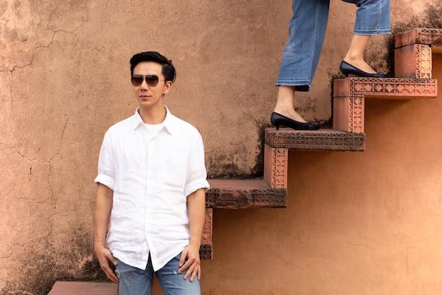 Equipe os óculos de sol vestindo que estão na escadaria com a mulher que anda acima das escadas.