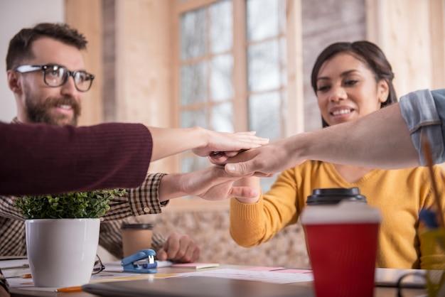 Equipe perfeita. pessoas alegres, agradáveis e felizes sentadas à mesa e juntando as mãos enquanto fazem parte da equipe