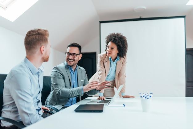Equipe positiva do negócio millenial que discute o projeto no quarto de reunião.