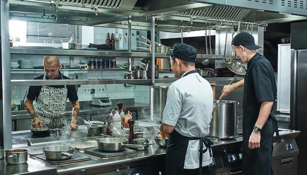Equipe profissional de chef e dois jovens auxiliares preparando comida na cozinha de um restaurante