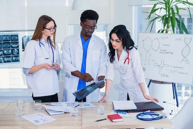 Equipe profissional de médicos multirraciais, tendo uma conferência. multi grupo étnico de estudantes de medicina. conceito de cuidados de saúde e medicina.