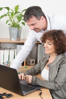 Equipe profissional homem e mulher trabalham juntos no laptop