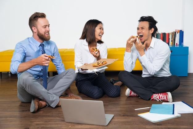 Equipe rindo que aprecia a pizza e se divertindo