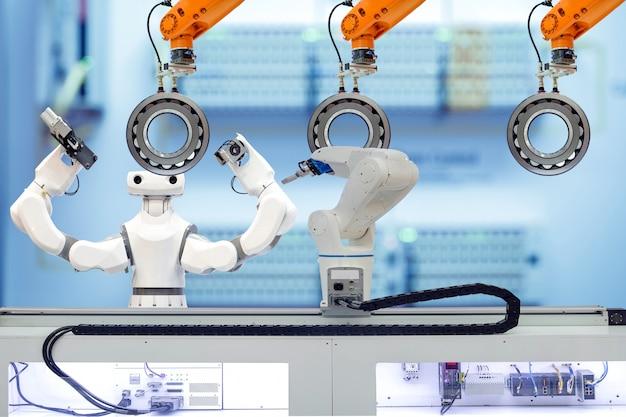 Equipe robótica industrial trabalhando com rolamento autocompensador de rolos através do robô de peça de trabalho em fábrica inteligente