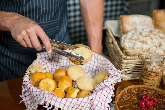 Equipe segurando biscoitos com tenaz em uma padaria