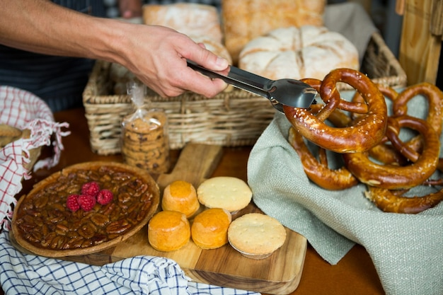 Equipe segurando pretzel com tenaz em uma padaria