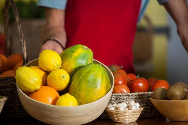 Equipe segurando uma tigela de frutas no balcão do mercado