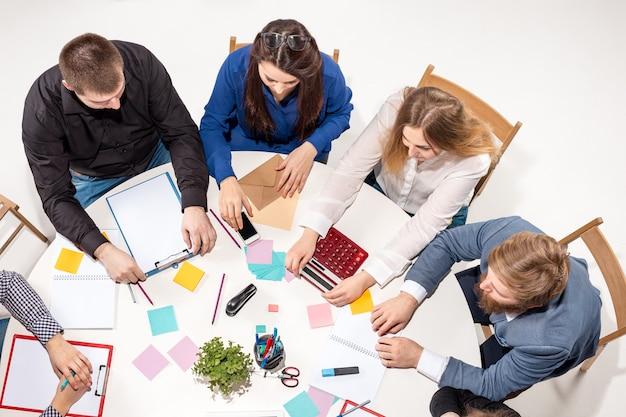 Equipe sentada atrás da mesa, verificando relatórios, conversando. vista do topo. o conceito de negócio de colaboração, trabalho em equipe, reunião