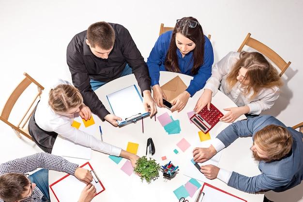 Equipe sentada atrás da mesa, verificando relatórios, conversando. vista do topo.