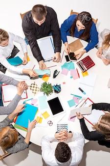 Equipe sentada atrás da mesa verificando relatórios, falando de vista superior