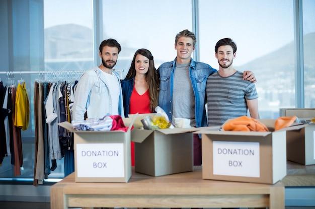 Equipe sorridente de negócios criativos em pé junto com a caixa de doações no escritório