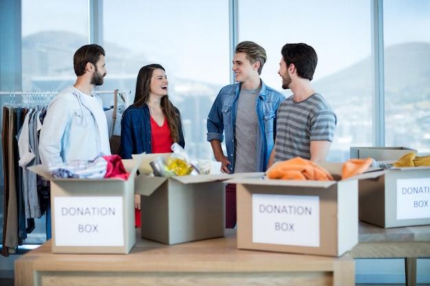 Equipe sorridente de negócios criativos falando perto da caixa de doações no escritório