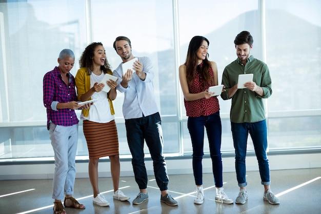 Equipe sorridente de negócios criativos usando tablet digital no escritório