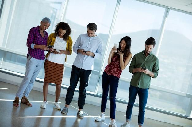 Equipe sorridente de negócios criativos usando telefone celular no escritório