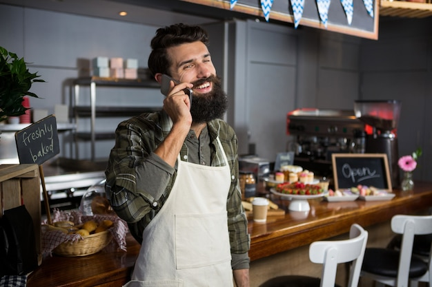 Equipe sorridente do sexo masculino falando no celular no balcão da cafeteria