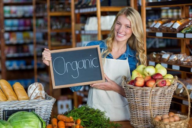 Equipe sorridente segurando placa de sinal orgânico na seção orgânica