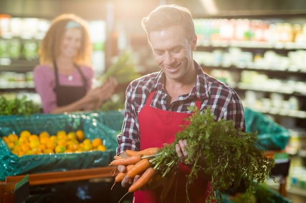 Equipe sorridente segurando um monte de cenouras na seção orgânica