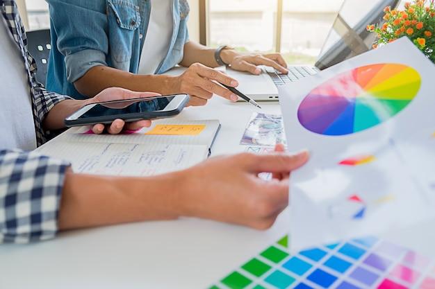 Equipe start-up criativa do desenhista de anúncio asiático que discute ideias no escritório.