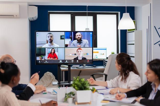 Equipe trabalhando por videochamada em grupo, compartilhando ideias, brainstorming, negociação, uso de videoconferência
