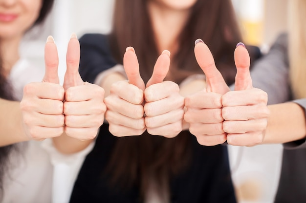 Equipe. três parceiros de negócios mantendo o polegar para cima