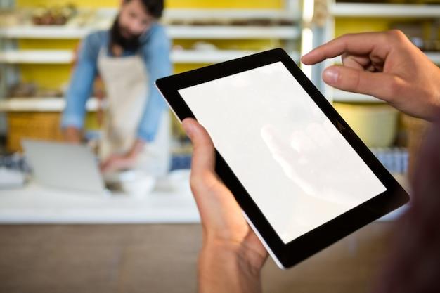 Equipe usando tablet digital no balcão da padaria