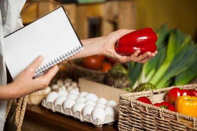 Equipe verificando pimentão vermelho na seção orgânica