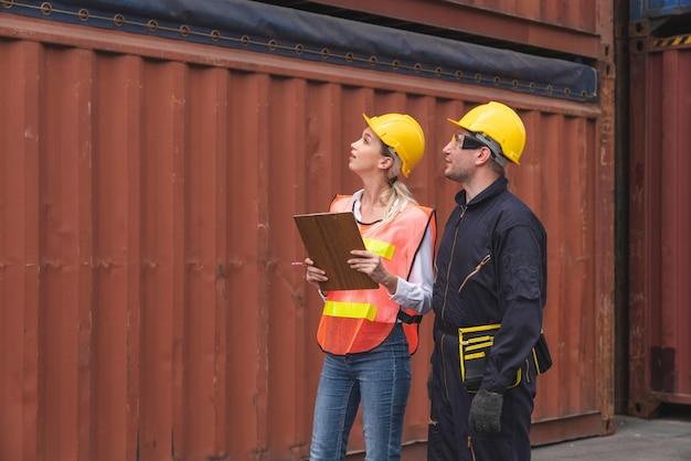 Equipes de logística masculinas e femininas, encontrando uma posição na caixa de documentos contêineres do navio cargueiro no transporte de contêineres