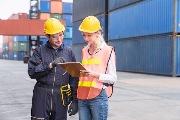 Equipes de logística masculinas e femininas, olhando a lista de verificação documentos da caixa de contêineres no navio de carga cargo no transporte de contêineres de carga