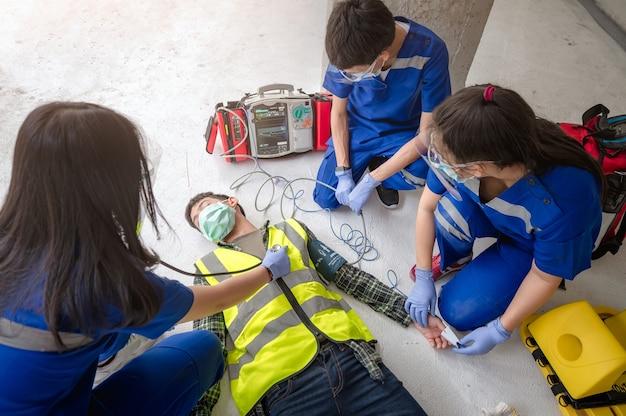 Equipes médicas de emergência estão ajudando pacientes inconscientes usando desfibriladores externos automatizados (aed) durante o resgate de trabalhadores inconscientes em um canteiro de obras.