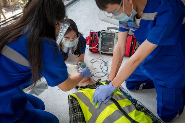 Equipes médicas de emergência estão ajudando pacientes inconscientes usando desfibriladores externos automatizados (aed) e fornecendo oxigênio. durante o resgate de trabalhadores inconscientes no canteiro de obras