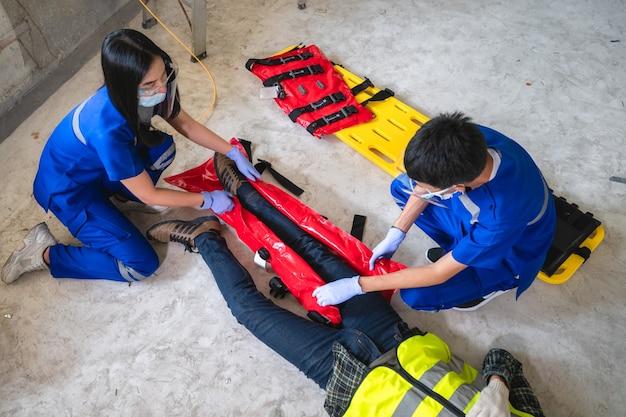 Equipes médicas de emergência estão ajudando um trabalhador da construção civil com um acidente na perna quebrada em um canteiro de obras. equipe de segurança ajuda acidente com funcionário.