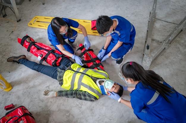 Equipes médicas de emergência são primeiros socorros para lesões em acidentes de trabalho usando equipamentos de primeiros socorros para suporte à perda de sensibilidade ou perda de movimento normal e perda de função nos membros