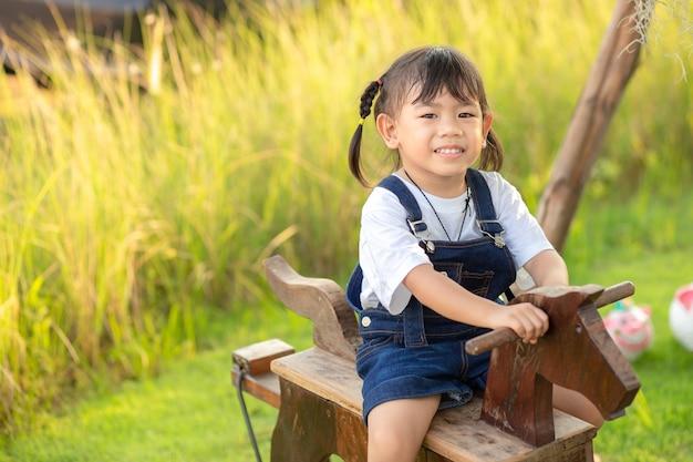 Equitação asiática da menina da criança pequena em um cavalo de madeira do brinquedo no jardim da grama verde.