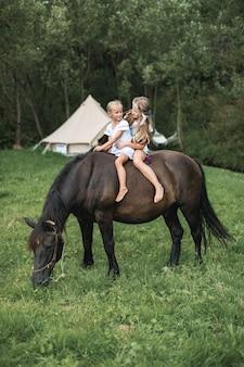 Equitação, retrato de duas lindas irmãs meninas em um cavalo escuro, ao ar livre no campo